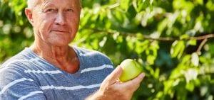 Older gentleman holding green apple, wealthy flourishing, productive financial advise