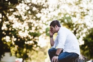 Mortgage SMI Stressed Man about mortgage sitting on log with white shirt - support for mortgage interest
