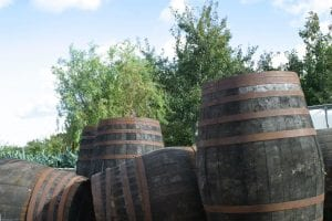 Aged Wooden Cider Barrels in Front of apple orchard Somerset 1st Financial Group Somerset Advisers